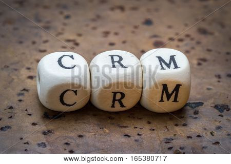 Crm (customer Relationship Management) Text On Wooden Cubes On A Brown Cork Background