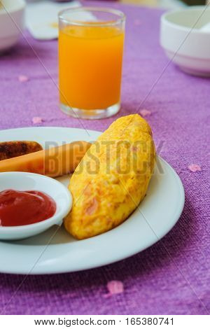 Delicious breakfast at hotel omelette sausage and oragne juice.