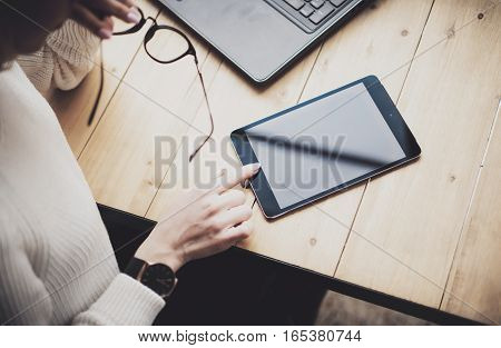 Top view of female hand touching digital tablet on the wooden table.Concept young business people using mobile devices.Horizontal, blurred background
