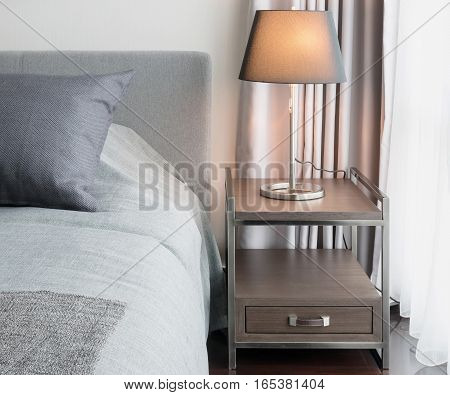 Stylish Bedroom Interior Design With Decorative Table Lamp And Grey Pillows On Bed