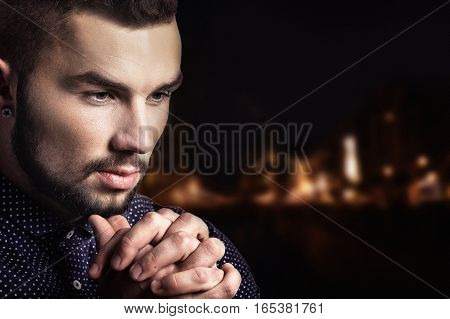 Potrait of handsome thoughtful young man on dark background
