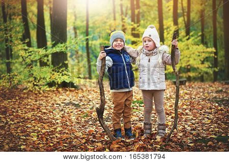 Two Hugging Children Holding Branches In Forest