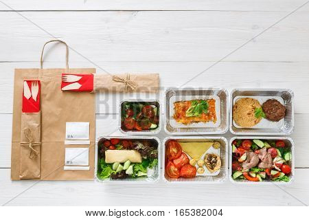 Healthy food delivery. Take away of natural organic fitness dishes for diet. Daily ratio nutrition meals in foil boxes on white wood. Craft package, meat and salads. Top view, flat lay