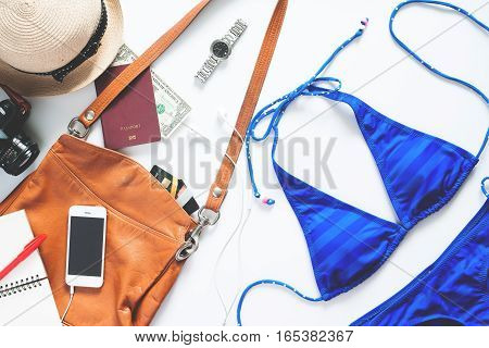 Set of summer items. Sexy blue stripe bikini with mobile phone camera and passport for summer vacation on white background