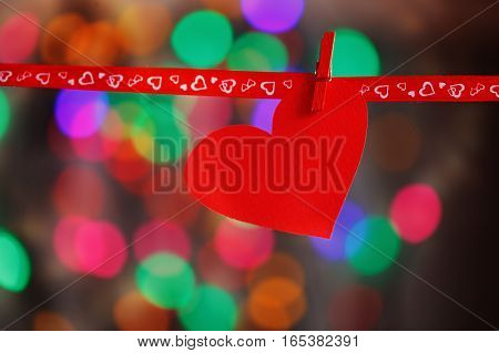 Red Paper heart hanging on red ribbon on colorful background. Concept Valentines day