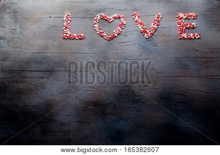 Word Love made with small candy hearts, pink, red, whie colors, on dark background. Valentine's day concept. Top view, copy space, horizontal