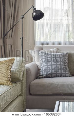 Corner Seat With Pattern Pillows And Black Retro Lamp