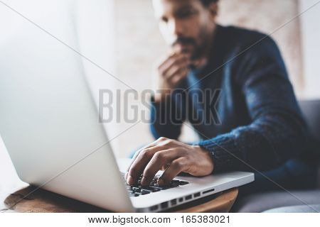 Attractive bearded African man using laptop while sitting on sofa at his modern home office.Concept of young people enjoying mobile devices.Closeup with a focus on male hand.Blurred background