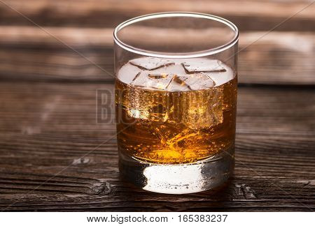 Glass of aperitif with ice on a wooden table