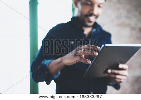 Attractive bearded African man using tablet while standing at his modern home office.Concept of young people enjoying mobile devices.Closeup with a focus male hand.Blurred background