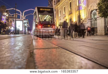 Seville Spain - January 1 2017: Streetcar that runs along downtown at night with Christmas decoration Seville Spain. Motion blurred