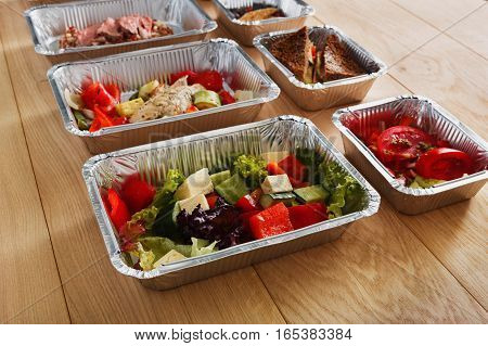 Healthy eating, diet concept. Take away organic restaurant food delivery. Weight loss nutrition in foil boxes. Vegetable salad on white wood