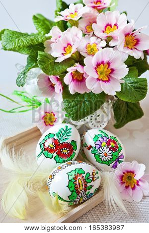Traditional Czech easter decoration - my handmade painted eggs with spring pink primrose flowers and white feathers. Spring easter holiday arrangement.