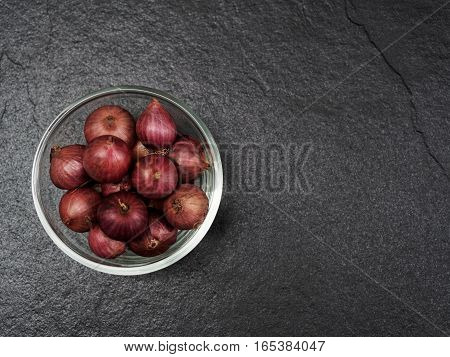 Shallot in a glass bowl with dark background