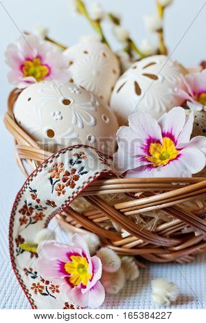 Traditional Czech easter decoration - white perforated lacy eggs in wicker nest with spring primrose flowers and floral ribbon