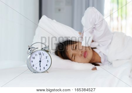 Sleepy young woman looking at alarm clock with hands covering her ears in the morning. early wake up.