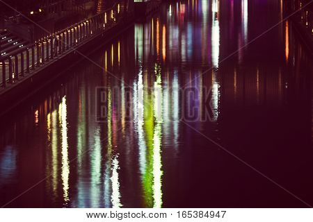 the reflection of light waves in the water Colored city lights reflected on water surface in night.