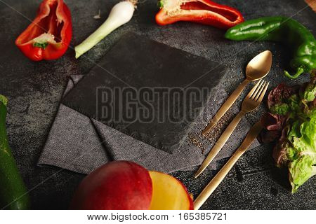 Peppers, leeks, zucchini and mango with golden utensils lying around an empty black slate board on black background, side view presentation with space for your text in center