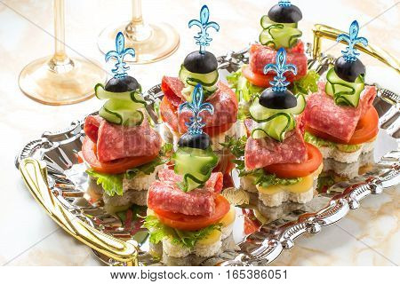 Colorful canape on skewers with vegetables and sausage on the tray. Tasty appetizer for a party or banquet