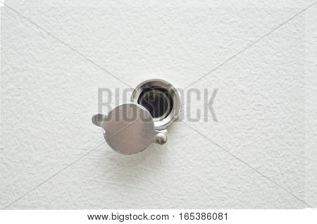 close up door lens peephole on white wooden texture