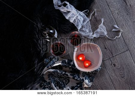 Two wine glasses heart shaped candles lingerie scattered in a party aftermath on silk and fur on floor horizontal top view