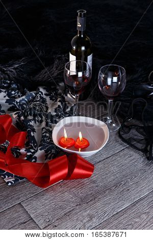Two wine glasses heart shaped candles lingerie scattered in a party aftermath on silk and fur on floor front view