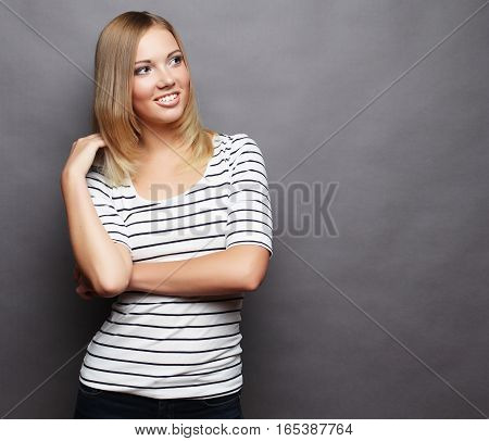 Beautiful smiling young woman.Over grey background.Studio shoot.
