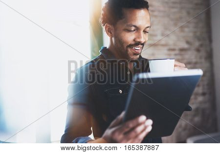 Closeup of young bearded African man using tablet while holding white ceramic cup in hand at modern coworking office.Concept people working with mobile gadget.Blurred brick wall on the background