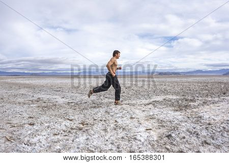 Fit and muscular Caucasian man runs shirtless in black pants and sandals over white salt flats of barren desert floor in Mojave Desert of California on cloudy day