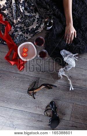 Two wine glasses heart shaped candles lingerie shoes scattered in a party aftermath on silk and fur on floor female hand rest on fur top view