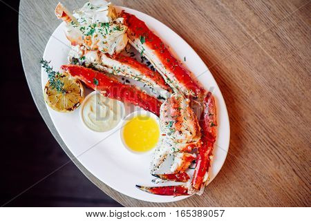 King Crab Cluster with sauces over wooden backround