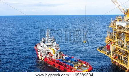Oil and Gas processing platform,crane lifting cargo to loading to supply boat over the sea