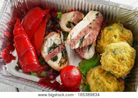 Healthy food restaurant delivery and diet concept. Take away of fitness meal. Weight loss lunch in foil boxes. Stuffed turkey with vegetables and other dishes at white wood