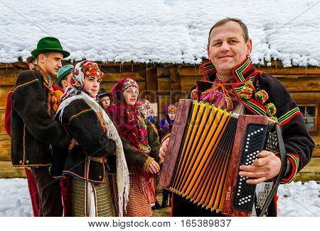Uzhgorod Ukraine - January 15 2017: Member of folklore band plays accordion during the seventh ethnic festival Christmas Carols in the old village. During the festival visitors can familiarize with a variety of Christmas customs caroling and celebrations