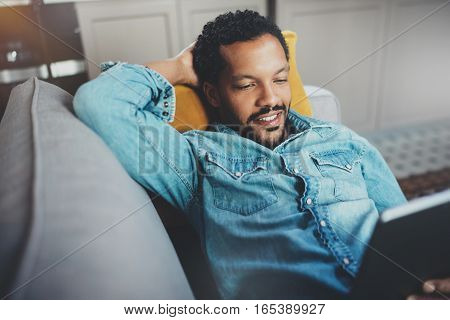Happy young bearded African man spending rest time in sofa and looking at tablet modern home.Concept of people enjoying mobile devices.Blurred background, closeup view