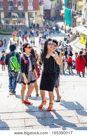 Macau, China - December 8, 2016: typical asian women with branded clothes and luxury accessories on staircase of Ruins of St. Paul's.On background, historic center of Macau popular tourist destination