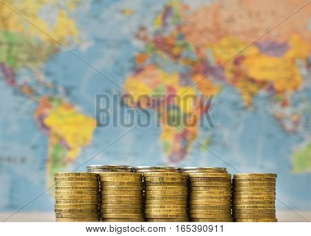 Metal Coins On A Background Map Of The World.