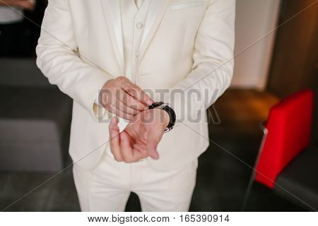 The man in the white suit wears watches on hand
