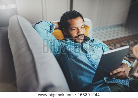 Young bearded African man spending chill time in sofa and looking at tablet modern apartment.Concept of people enjoying mobile devices.Blurred background