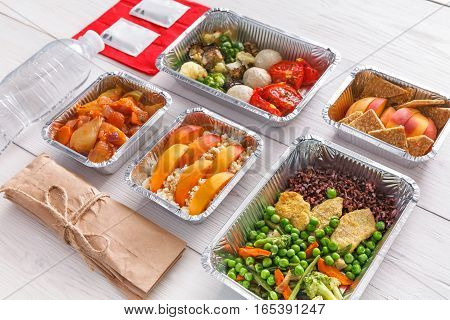 Healthy restaurant food. Chef prepared diet daily meals delivery. Fitness nutrition, vegetables, meat and fruits in foil boxes, cutlery, water and package. Dishes on wood