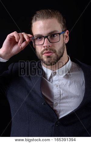 handsome bearded stylish business man portrait in elegant black suit posing in glasses in studio on black background