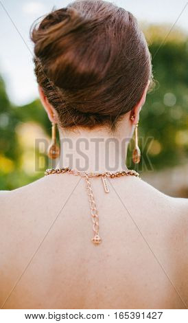 Girl with a high hairstyle and ornament on a neck