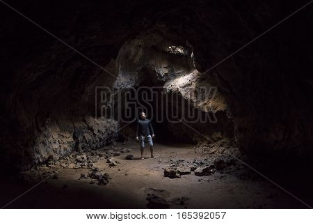 Man stands in eerie underground cave looking up at hole in ceiling pouring in sunlight at Mojave lava tubes in California