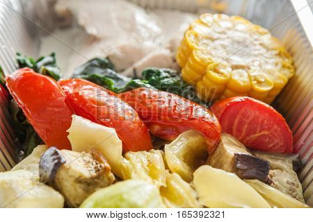 Healthy food restaurant delivery and diet concept. Take away of fitness meal. Weight loss lunch in foil box closeup. Boiled turkey and steamed vegetables on white wood