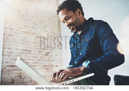 Bearded young African man smiling and using laptop while sitting at his modern coworking place. Concept of happy business people. Blurred background, flare effect