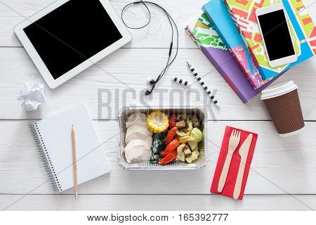 Healthy lunch and diet concept. Take away food in foil box, tablet and mobile phone with copy space, earphones and dairy on table of school student. Meat with vegetables, top view on white wood