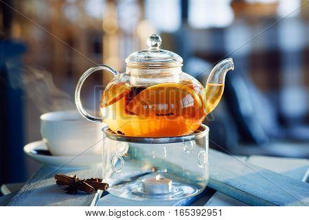 Hot tea with orange and cinnamon over blue vintage backround