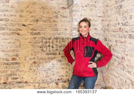Craftswoman In Front Of Brick Wall In Bare Brickwork