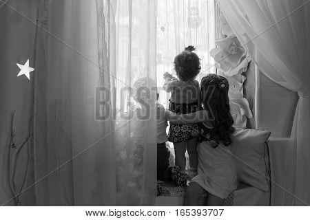 children friends sitting back in the winter window Christmas