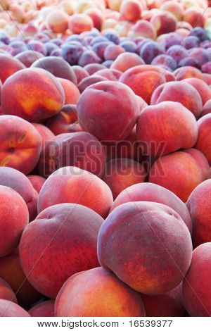 Piles of red, oraange, burgandy peaches at the farmers market